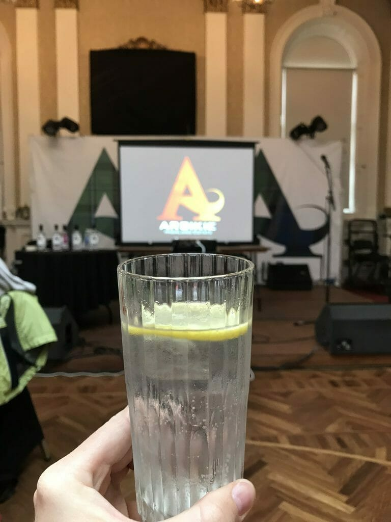 Gin and tonic in front of the screen showing the Arbikie logo