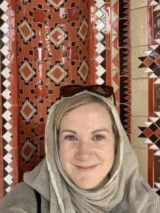 Katie taking a selfie in headscarf in front of geometric patterned tiles
