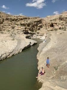 Couple on the rocks at the side of Wadi Bani Khalid