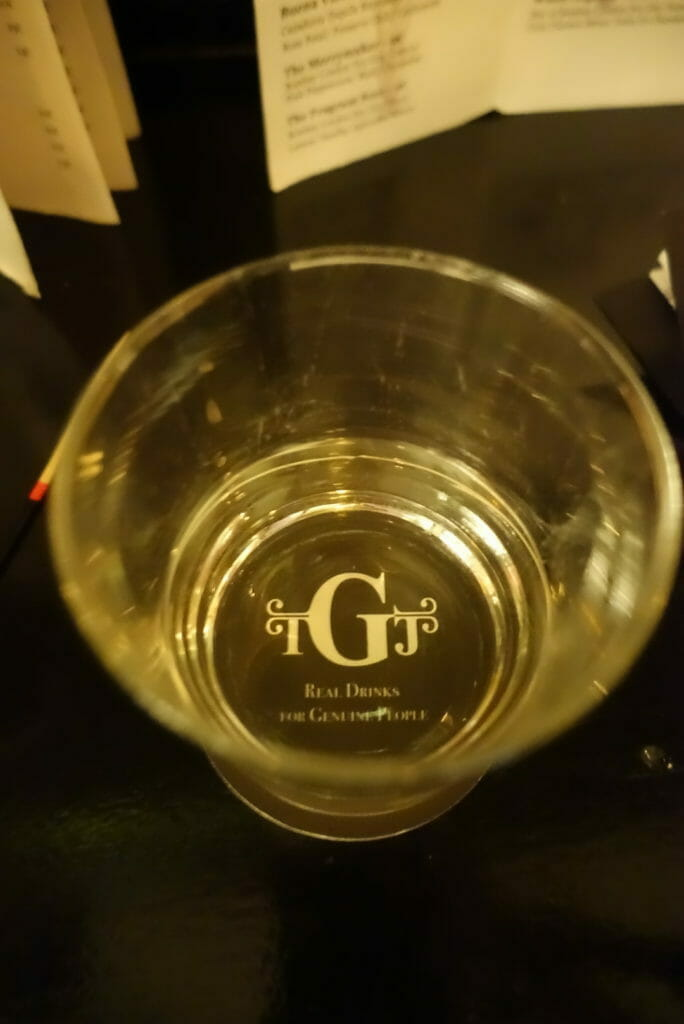 The Gin Joint logo under a glass