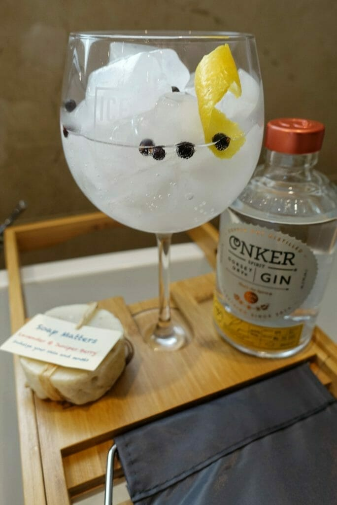 Ice and a Slice gin glass on the bath tray with Conker gin bottle and soap