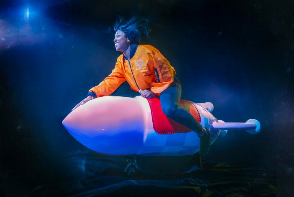 Girl riding a pink space rocket