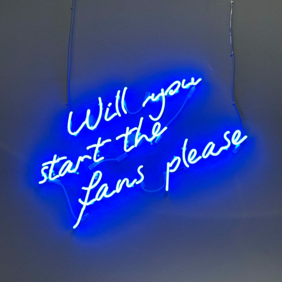 'Will you start the fans please' in neon lights