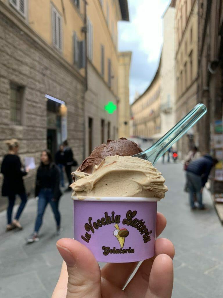 Pot of gelato in front of a Siena street