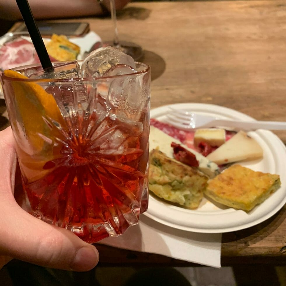 Negroni cocktail in front of a plate of cheese, ham and other snacks