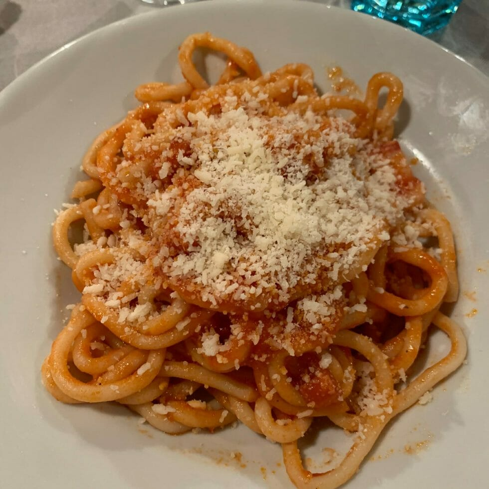 Pici with a tomato & bacon sauce topped with parmesan