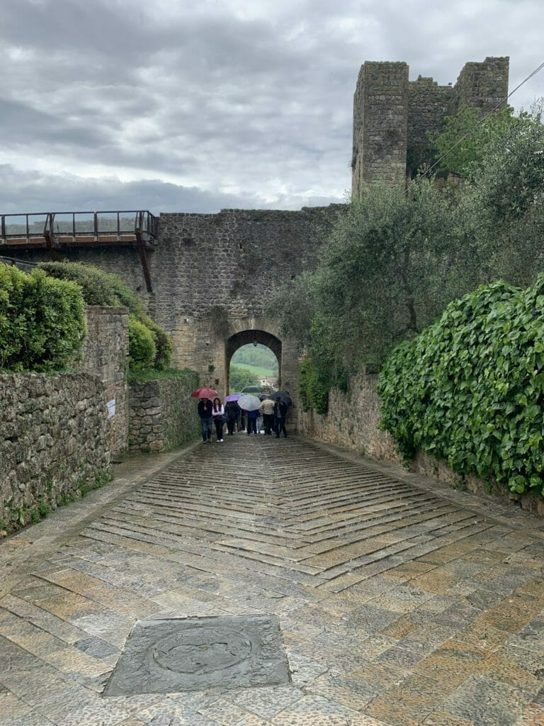 Tourists with umbrellas in front of the town wall & gateway