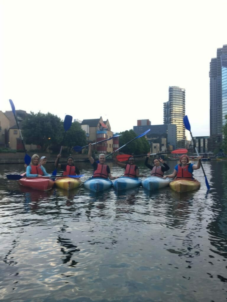 The whole class lined up in kayaks with paddles raised in salute