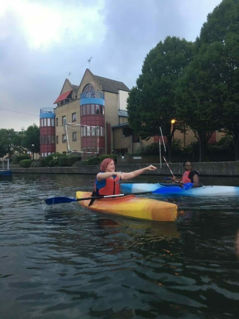 Katie in mid throw in her kayak