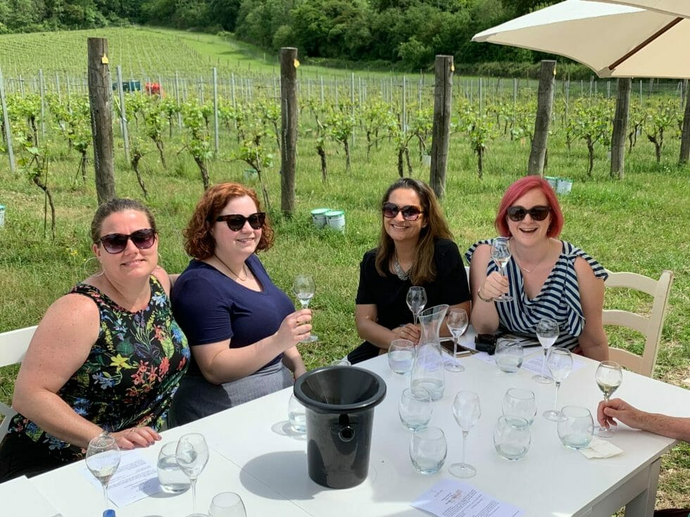 Katie and friends sitting outside in the vineyard for the wine tasting