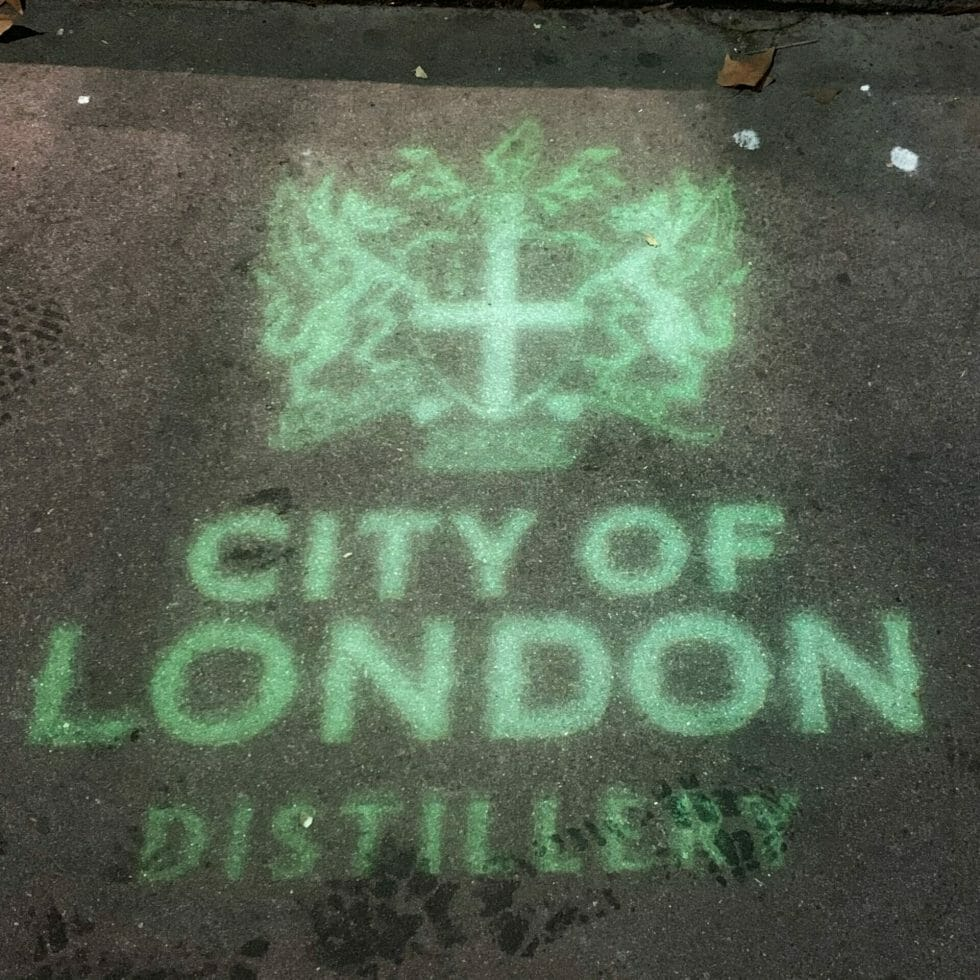 Green projection of the City of London coat of arms and distillery name on the pavement