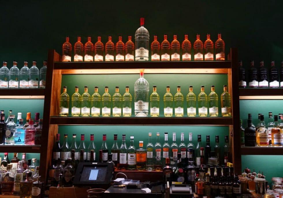 COLD gin bottles lit up on display on the back bar