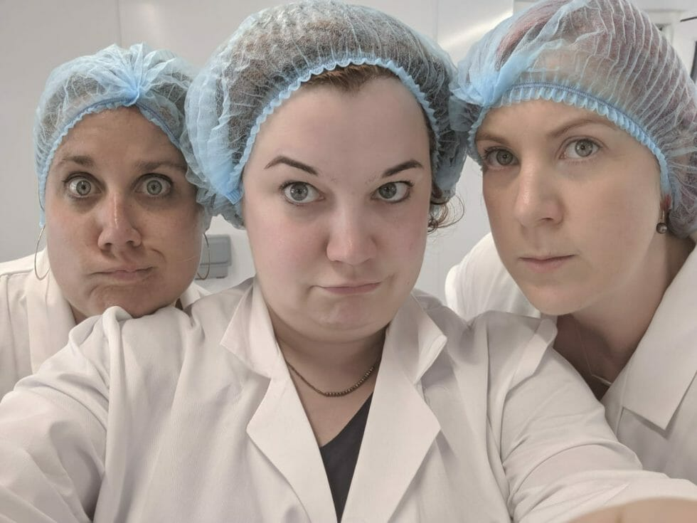 Katie and friends in hair nets and white lab coats