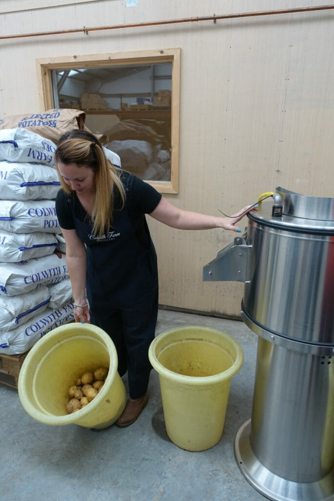 Tour guide Kim with potatoes and the machine that cleans and peels