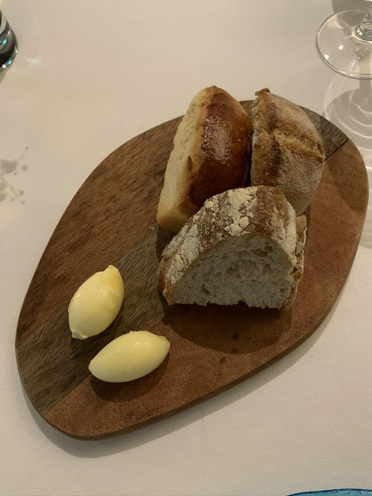 Wooden board with bread and butter