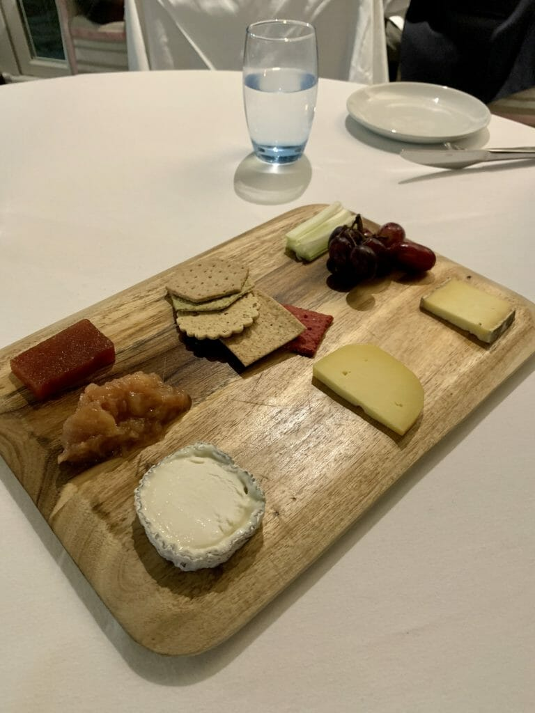 Cheese presented with crackers and fruit on a wooden board