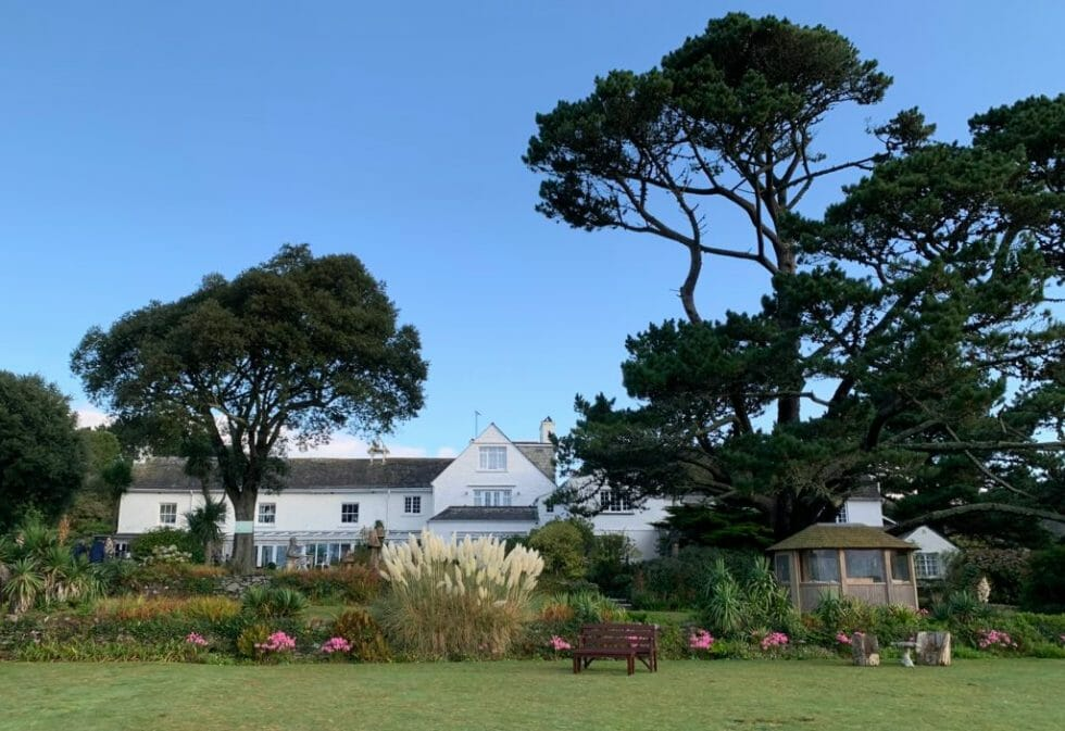 The white painted Talland Bay hotel framed by gardens and pine trees