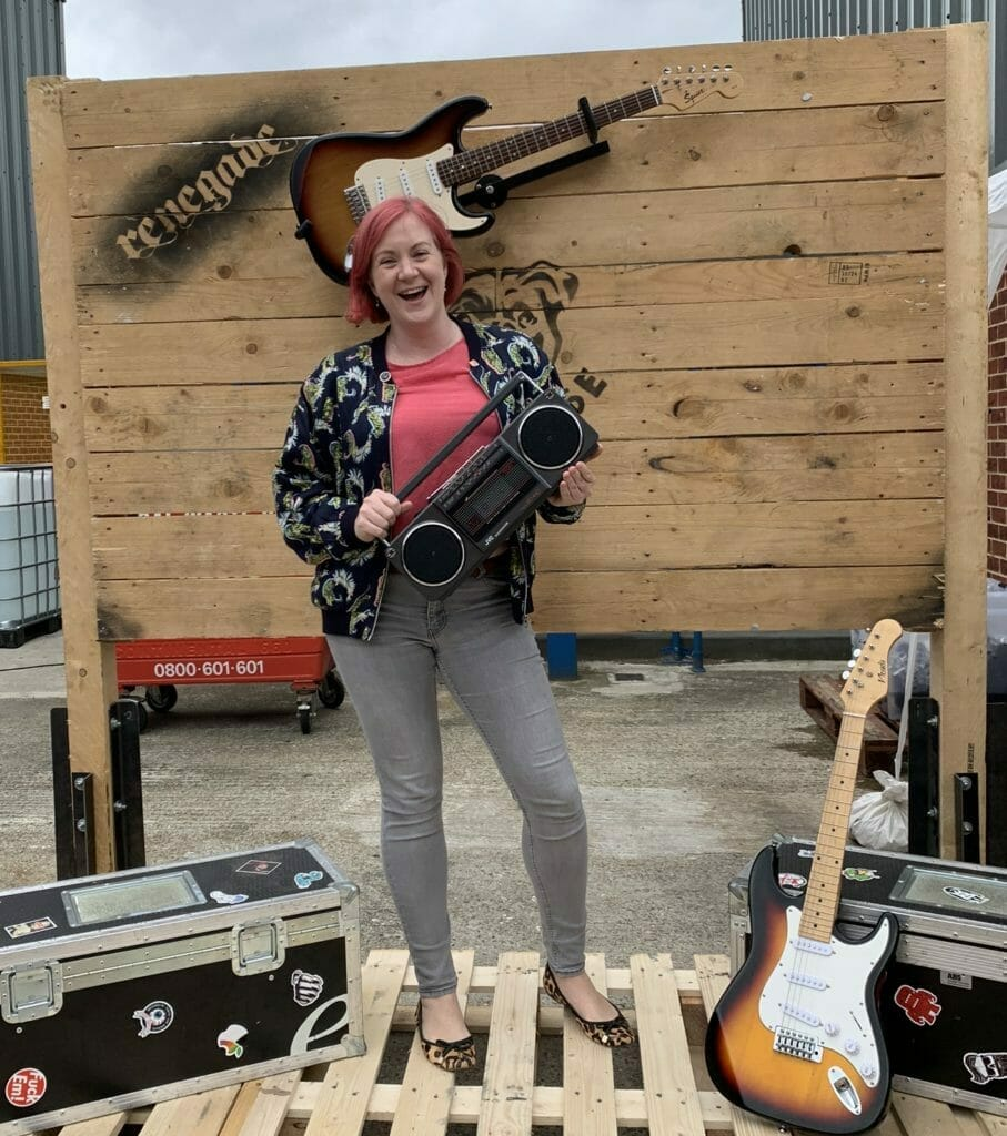 Katie posing with music props at Dog House Distillery