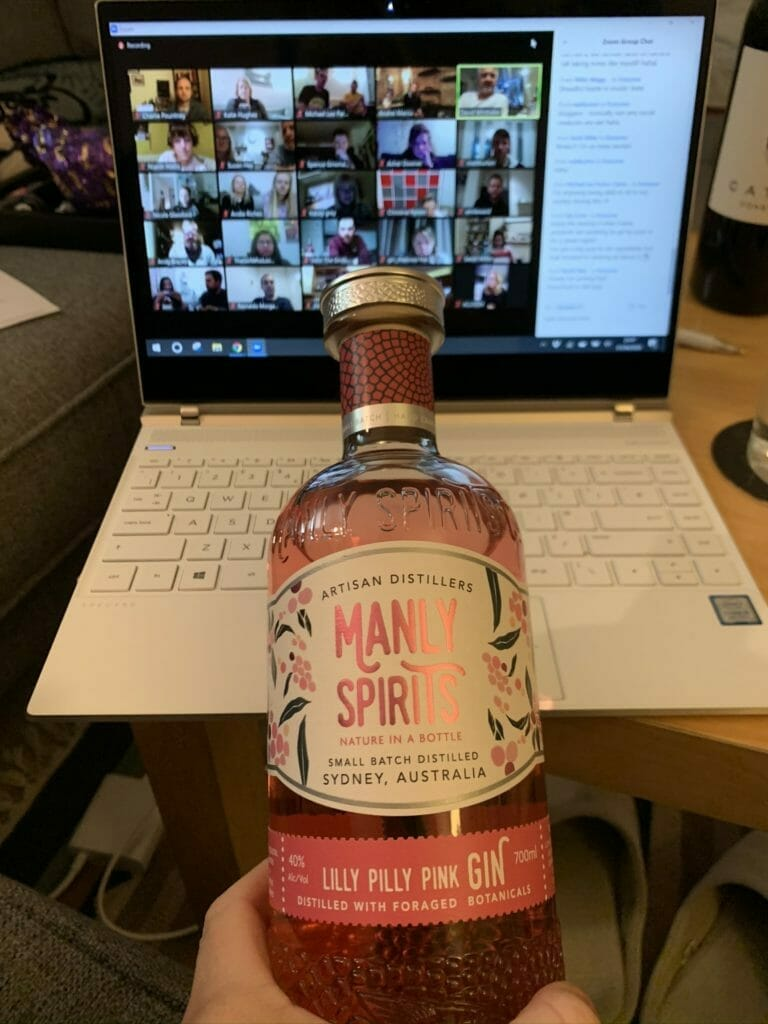 Computer with thumbnails of people's images and bottle of Lilly Pilly in front