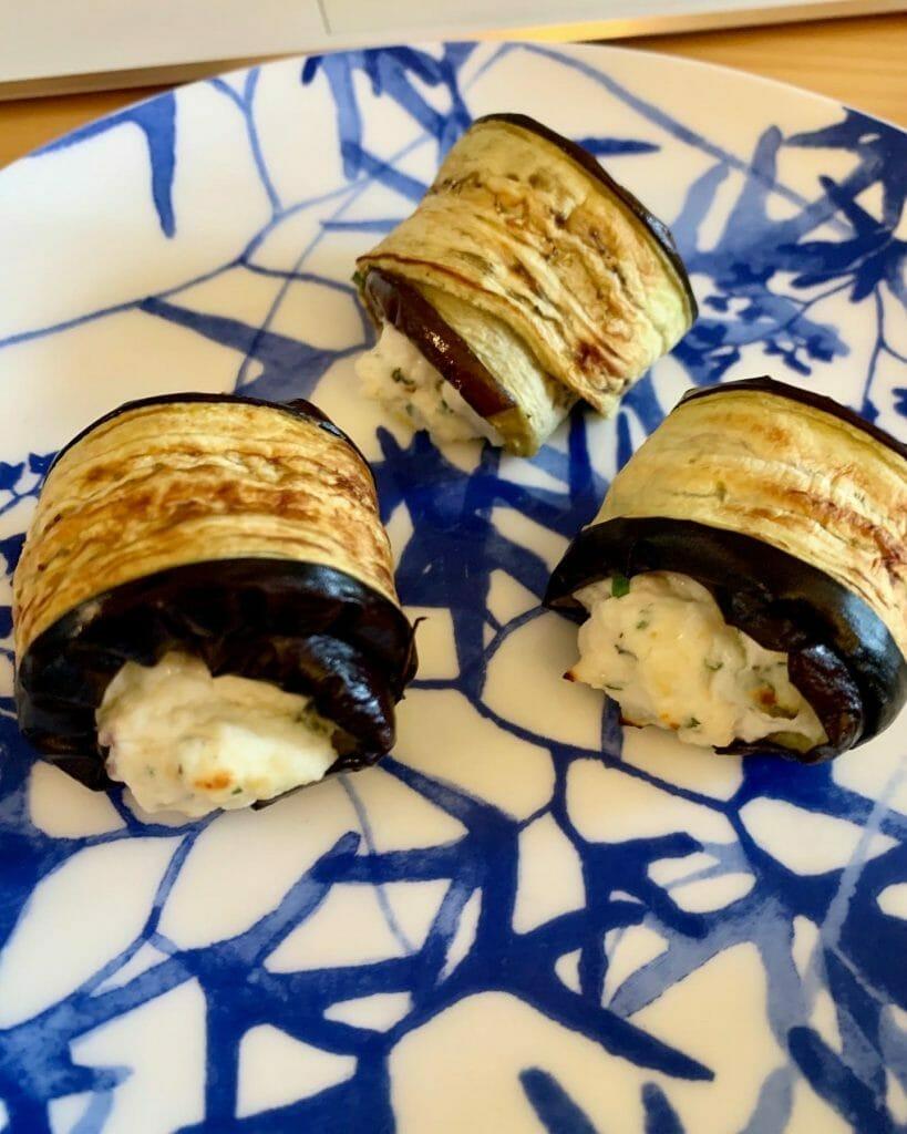 Three aubergine rolls on a plate
