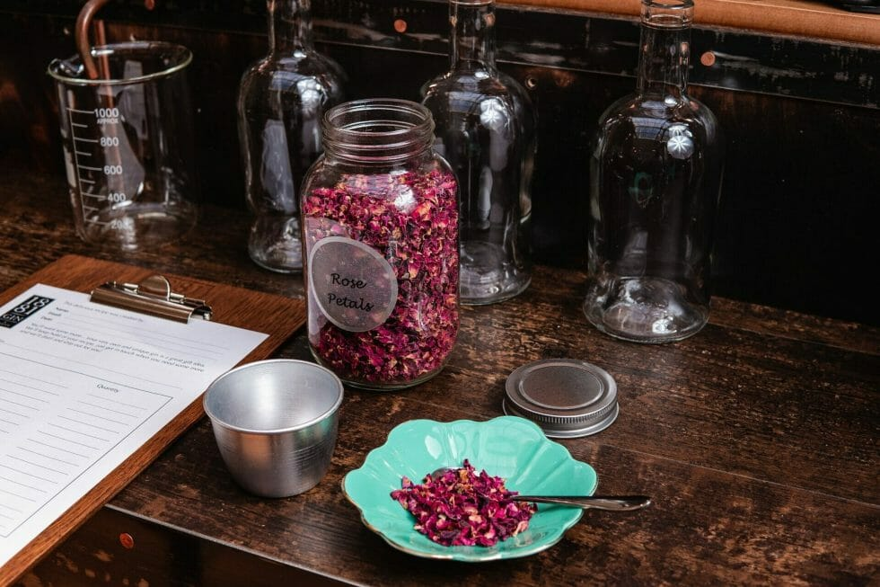 Measuring out rose petals to go in the still