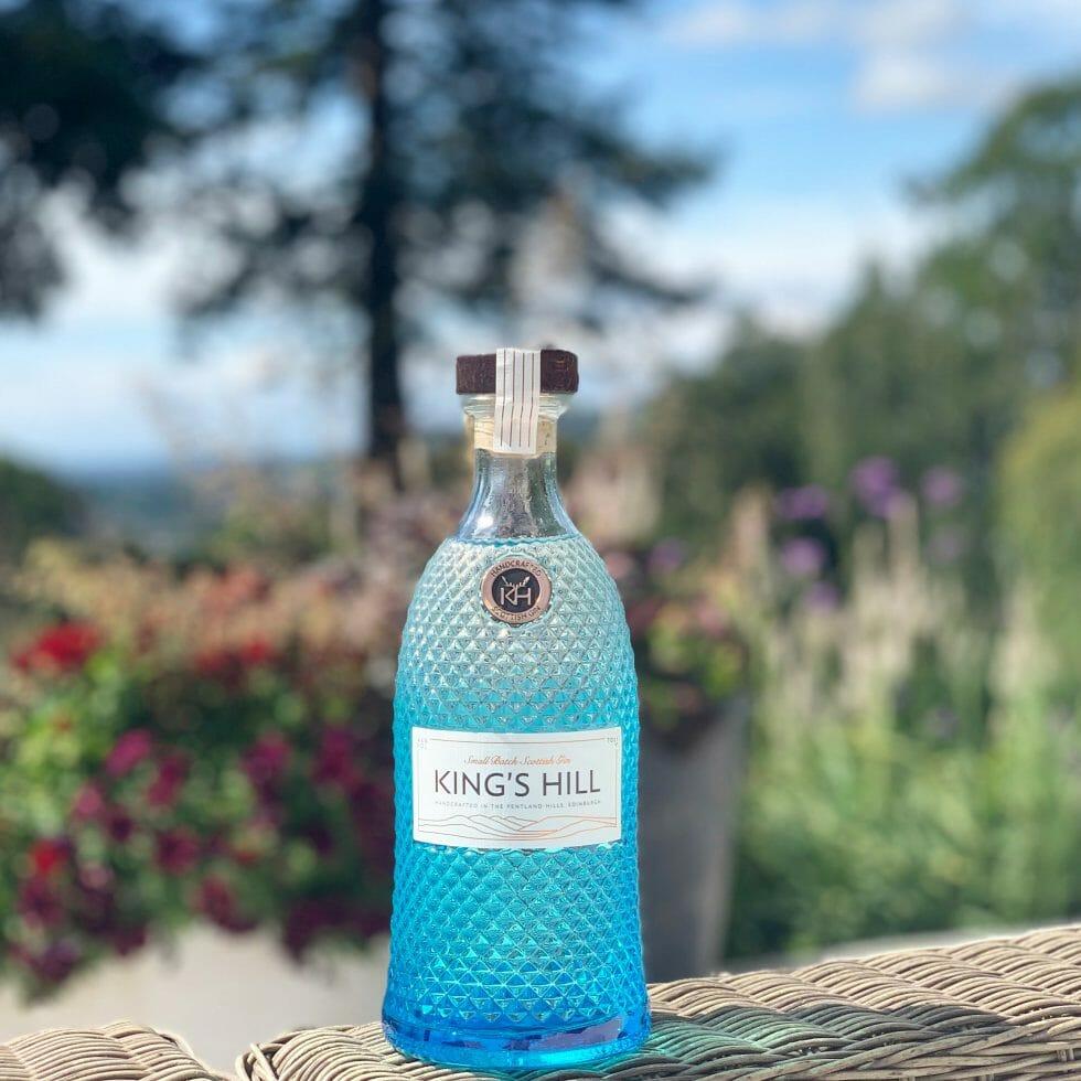 King's Hill gin blue diamond pattern bottle in front of landscape shot