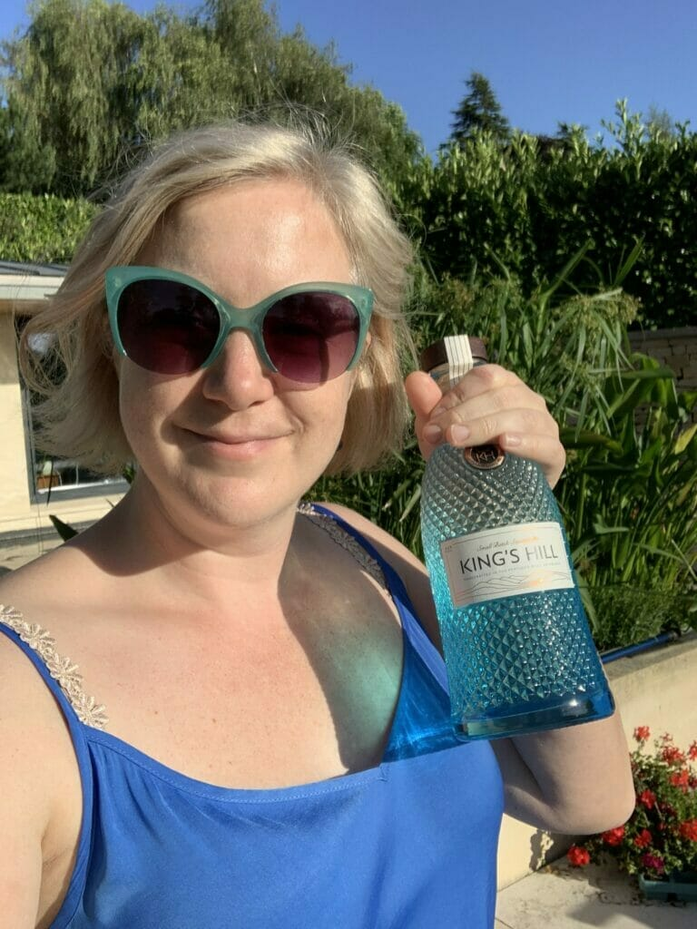 Katie holding the blue bottle with blue top and aqua sunglasses