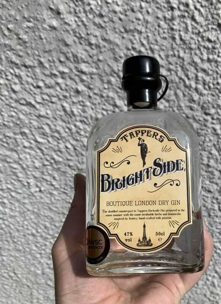 Tappers Brightside gin held up in front of a white wall