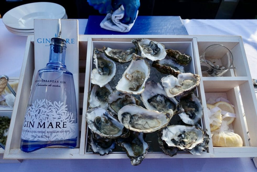Box of opened oysters next to Gin Mare bottle and lemons