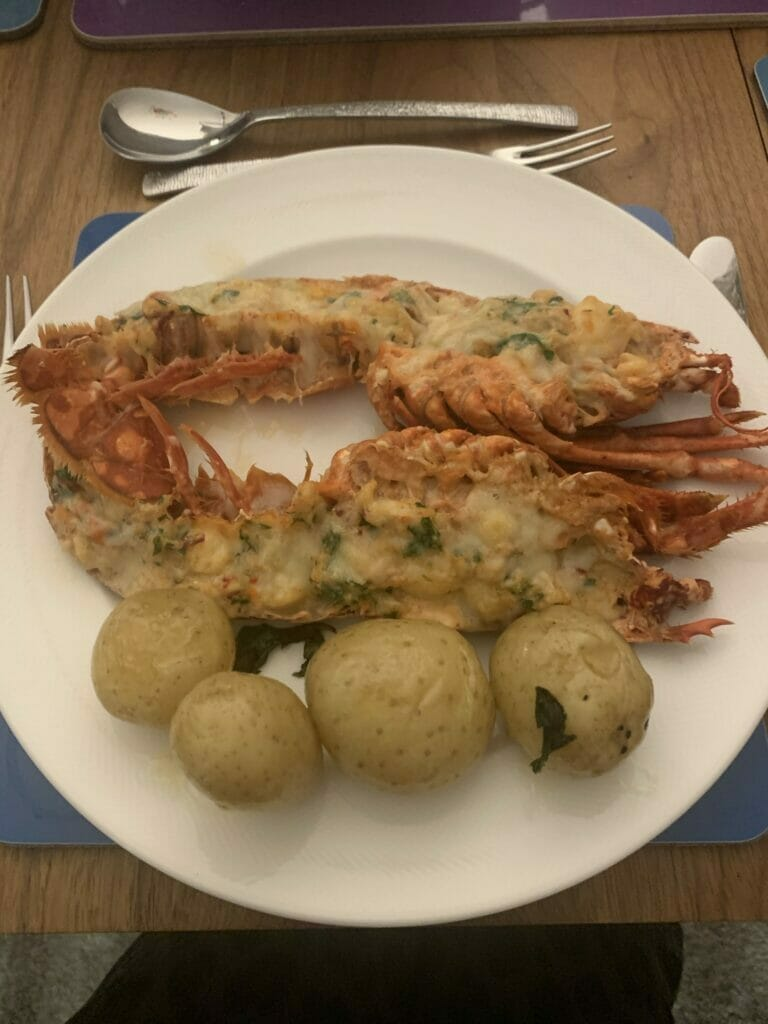 Lobster Thermidor with new potatoes on a plate