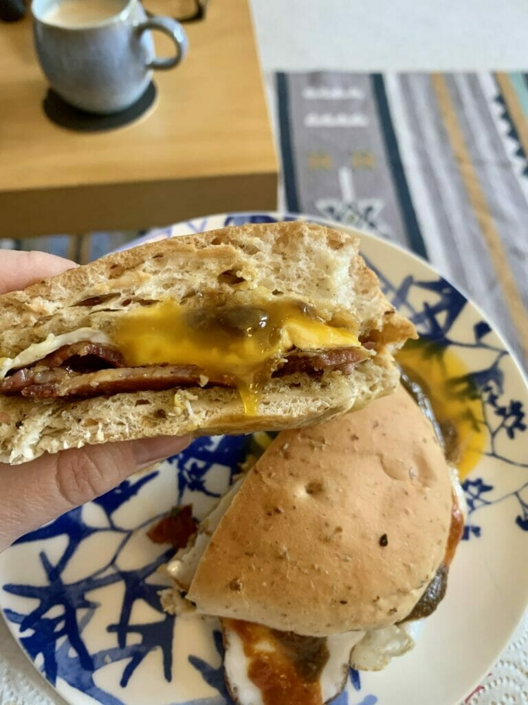 Half the bacon bun with egg yolk oozing out and a cup of coffee in the background