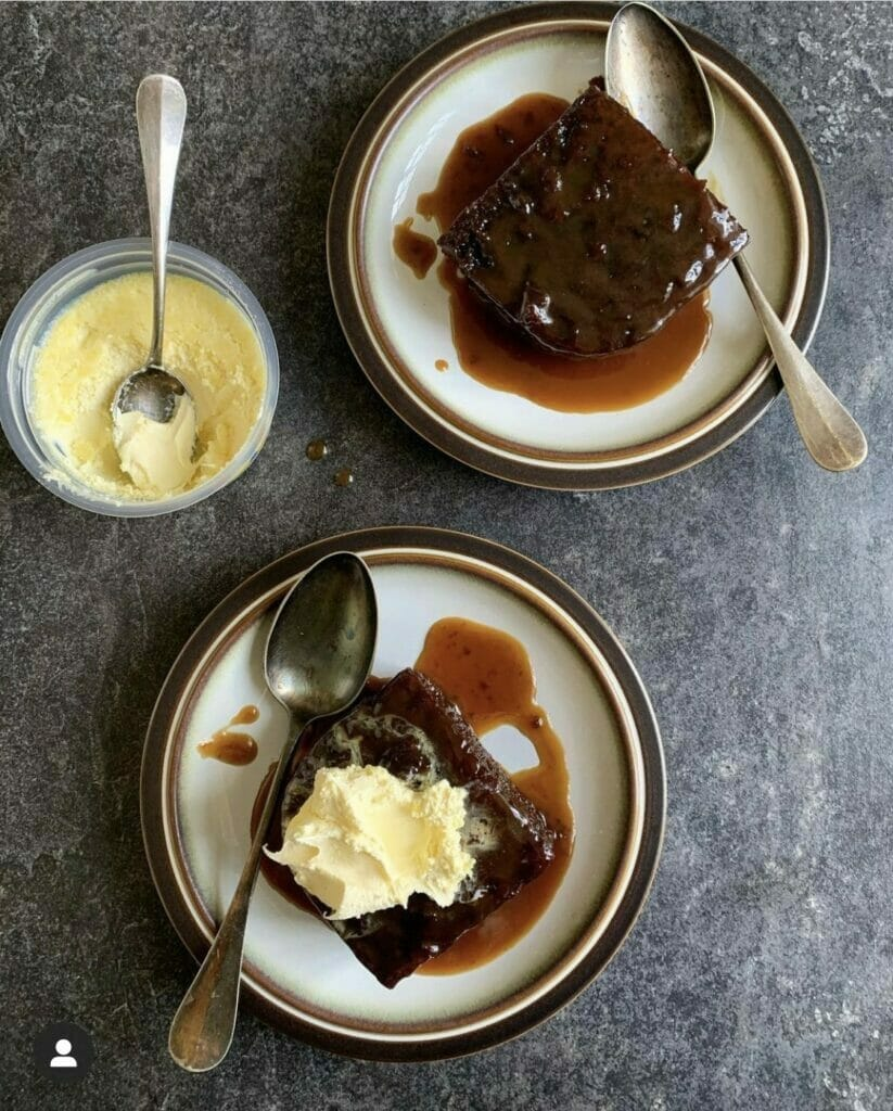 2 plates of sticky toffee pudding with clotted cream