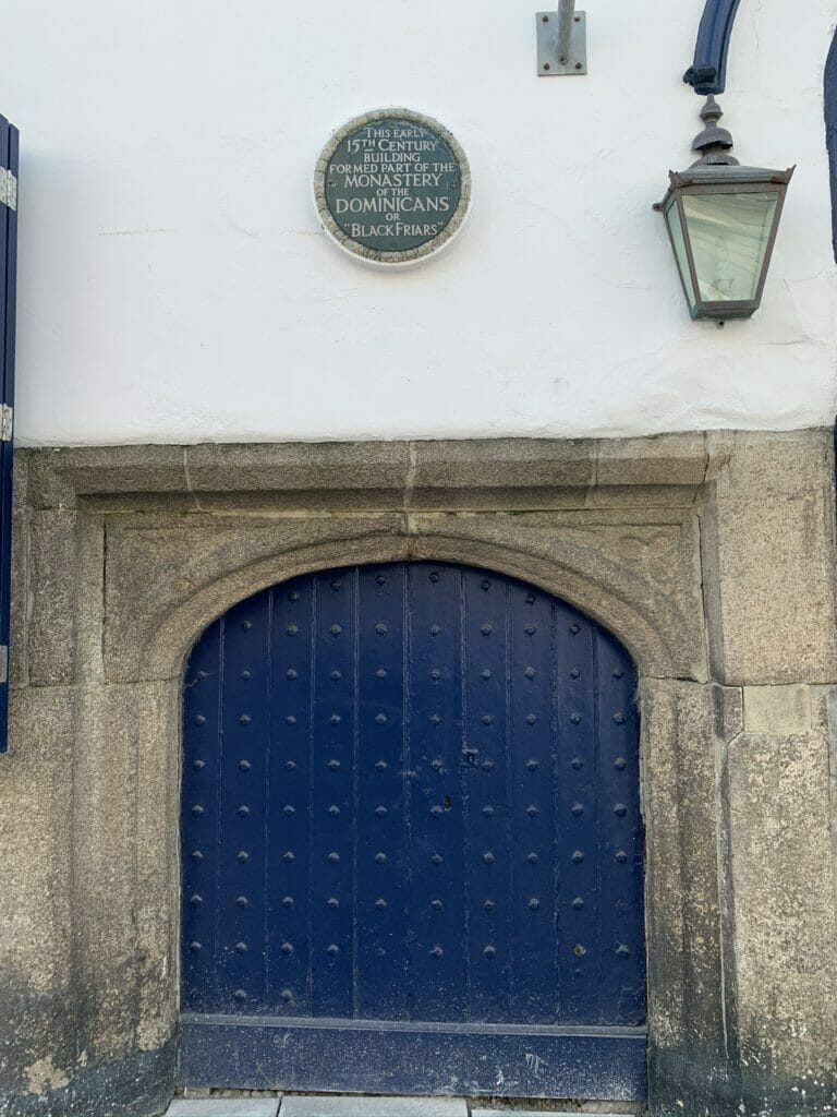 Blue plaque saying the building was part of the monastery above a blue door