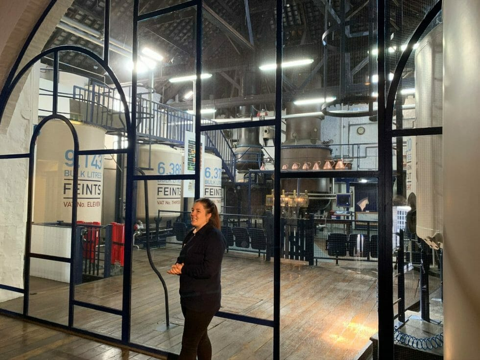 Tour guide in front of the windows leading to the working part of the distillery