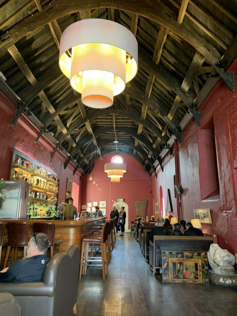 Large high ceiling room with dark beams and the bar running along the side