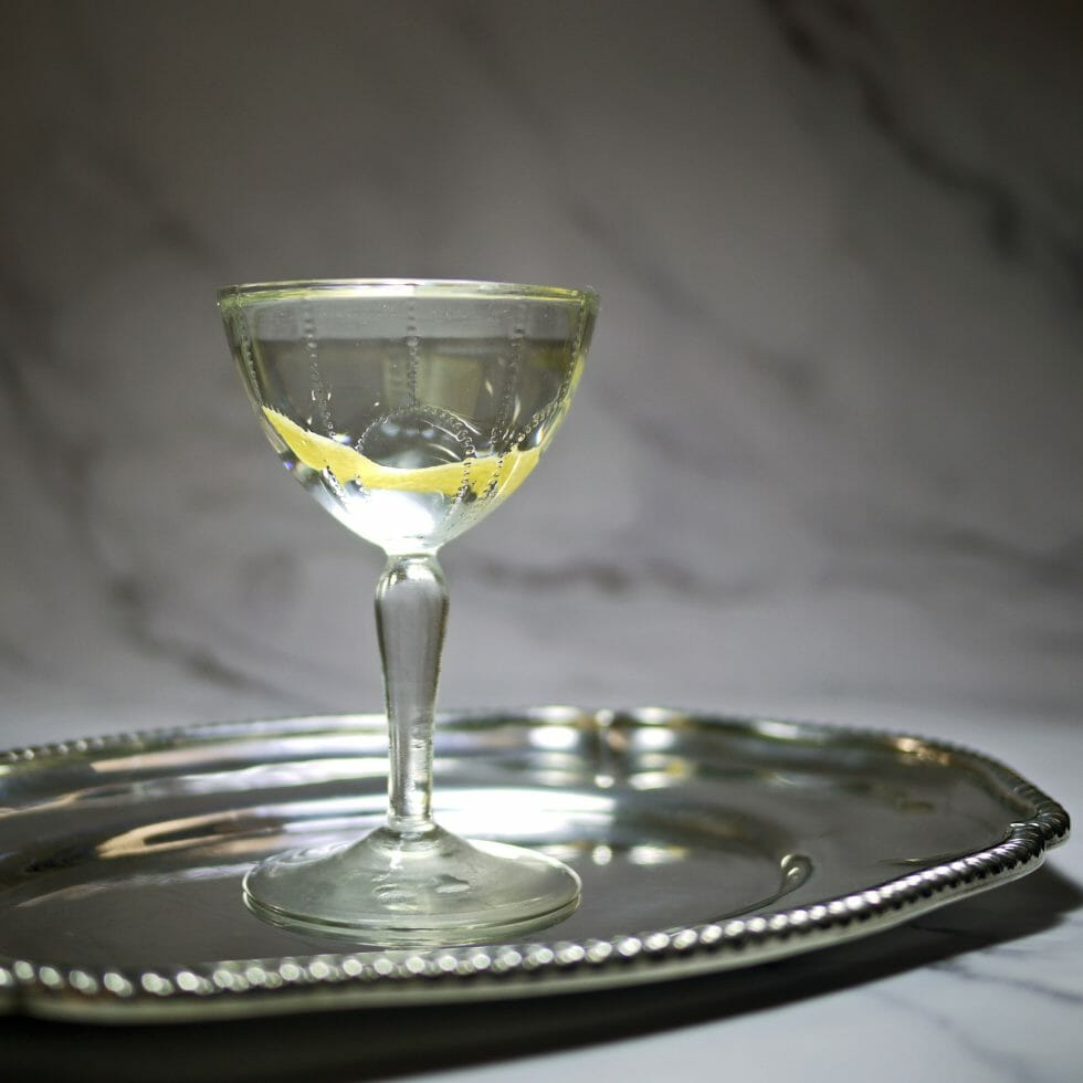 Martini in a vintage glass on a tray with lemon peel garnish